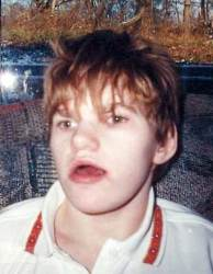 Photo of Casey Axsom, a young adult with short, messy strawberry-blonde hair, wearing a white polo shirt. Casey's mouth is slightly open.