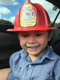 Photo of Ahziya, a smiling toddler in a plastic fireman's hat.