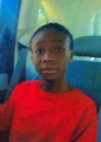 Photo of Alexis Agyepong-Glover, a girl in a bright red shirt, her hair pulled neatly back into a ponytail.