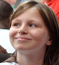 Photo of Zahra Baker, a girl with straight brown hair and freckles, smiling at something to the left of the viewer.