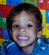 Photo of Brandon Williams, a young boy, in front of a brightly colored alphabet mural.