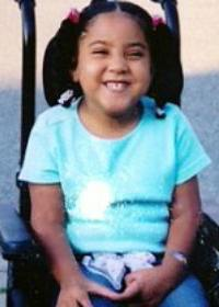 Photo of Julie Cirella, a girl wearing pigtails and sitting in a power chair.