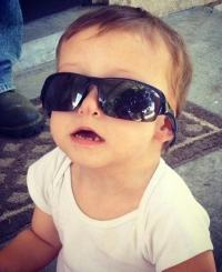 Photo of Hayden, a toddler wearing a too-big set of sunglasses.