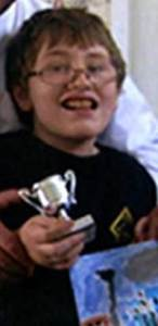 Glen Freaney, a boy smiling awkwardly and holding a painting and a small silver trophy.