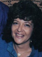 Photo of Pamela Hall, a middle-aged woman with curly black hair, wearing a blue shirt.