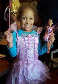 Photo of Heaven Woods, a little girl in a pink tutu, holding a doll.