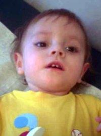 Gerren Isgrigg, a toddler wearing a yellow shirt, lying on a mat.