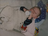 Photo of Jarrod Tutko Jr. as a baby, holding and drinking from a bottle.