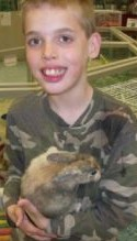Photo of Kyle Dutter, a boy wearing a camo top and holding a rabbit.