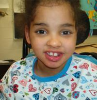 Photo of Lakesha Victor, a girl with a gap-toothed smile. Her head leans against a headrest.