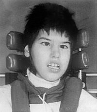 Black and white photo of Tracy Latimer, a teenager leaning against a headrest. She has short dark hair.