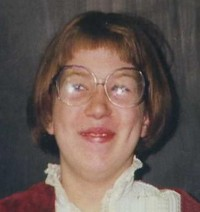 Photo of Laura Cummings, a woman wearing large glasses.