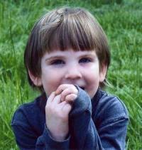 Photo of Marcus Fiesel, a small boy on a green lawn and with windswept hair. He is shyly covering his mouth with his hands.