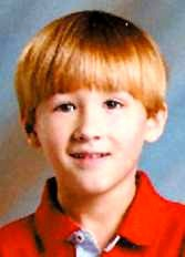 Photo of Mason Scott, a young boy wearing a bright red polo shirt.