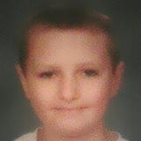 Photo of Michael Becht, a boy in a white shirt.