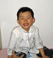 Photo of Scarlett Chen, a grinning Asian toddler with short hair.