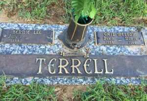 A gravestone made for a married couple, decorated with an urn for flowers. It reads: Terrell. Bernie Lee, Gail Melody. The death date for Bernie Lee is blank; the death date for Gail Melody is filled in. The dates are too small to make out.