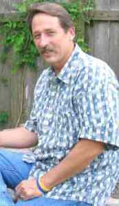 Photo of Lloyd Yarbrough, a middle-aged man in shirt and jeans. His hair is graying and he wears a mustache.