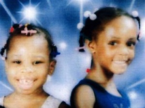 Portrait photo of Minnet and Jasmine Bowman. They are young girls with their hair in braids and barrettes, smiling at the camera.