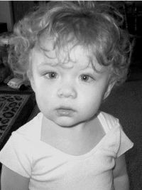 Black and white photo of Nikolas Chavez, a toddler with wispy, curly blonde hair, wearing a onesie and a puzzled expression.