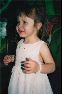 Photo of a little girl in a white dress. She is smiling at someone off the side of the image.
