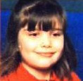 Photo of Molly Holt, a girl with straight brown hair, cut into bangs and tied back. She is smiling slightly.