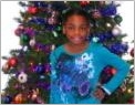 Photo of Tia Jones in front of a Christmas tree.