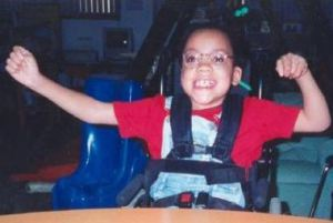 Photo of Danieal Kelly, a girl sitting in a wheelchair, smiling and waving her arms.