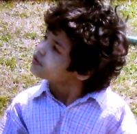 Photo of Joshua Mendoza, a small boy with wild, curly dark brown hair.