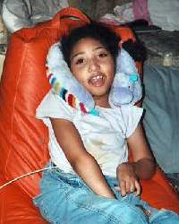 Photo of Makayla Norman, a teen girl sitting in a bean bag chair, with her head propped against a pillow.