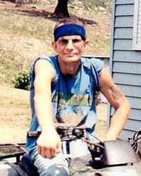 Photo of Jason Ritzert, an adult man wearing a headband and casual clothes and sitting on a dirt bike. He has a tattoo on his right arm.