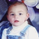 Portrait photo of a toddler girl in overalls, earrings, and a buzz cut.