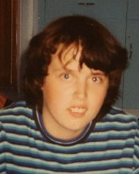 Photo of Michelle Thomson, a teenage girl with wavy brown hair, wearing a striped shirt.