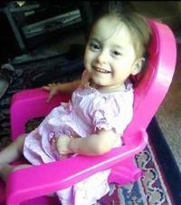 Photo of Stephanie Torres, a little girl sitting in a pink plastic chair.