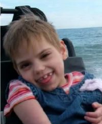 Photo of Meah Weidner, a young girl sitting in a power chair, smiling mischievously with her tongue stuck out. There is an ocean in the background.