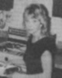 A blurry black-and-white photo of Lorraine Miranda. She is a young woman with curly light-colored hair, wearing a dark shirt.