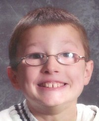 School photo of Isaiah Buckner, a boy wearing very thick glasses and smiling.