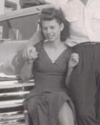 Black and white photo of a young woman sitting on the hood of a car.