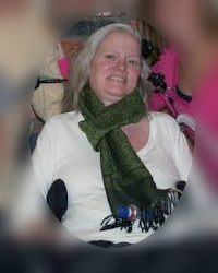 Photo of a gray-haired woman in a white shirt and big green scarf, sitting in a wheelchair.
