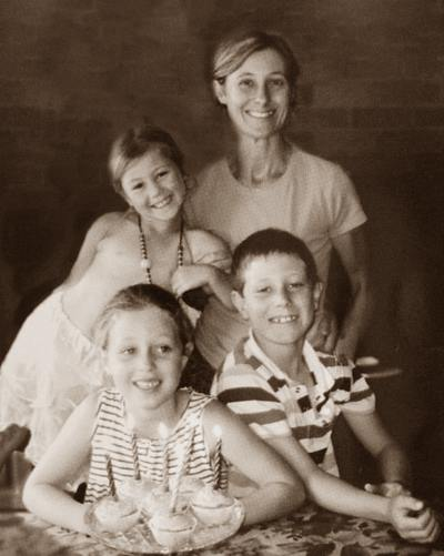 Sepia-tone portrait photo of a woman and three children, a boy and two girls. They are smiling at the camera.