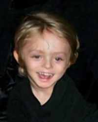 Photo of a toddler with short, light hair against a black background.