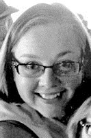 Black and white newspaper photo of a smiling girl with a round face and short, light hair. She is wearing glasses.