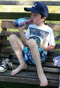 Photo of a thin boy sitting on a park bench, his shoes off and his feet drawn up onto the bench. He is wearing a baseball cap and drinking from a bottle of juice.