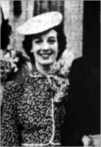 Grainy newspaper photo of a woman in an old-fashioned dress and hat; she looks to be in her twenties and is smiling.