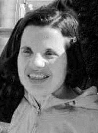 Black and white photo of Carmina Brown, a young woman with straight, dark hair and pale skin. She is squinting into the sun.
