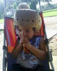 Photo of a toddler in a sling-style stroller. He is chewing on a raw carrot, and wearing a bulky helmet.