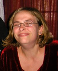 Photo of Christina Harms, a young blonde woman wearing glasses and smiling broadly.