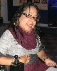 Photo of Melissa Torres, a woman with light brown skin, dark brown hair, and glasses. She wears large earrings and a maroon-and-gray sweater; in the foreground is a joystick for controlling her power wheelchair.